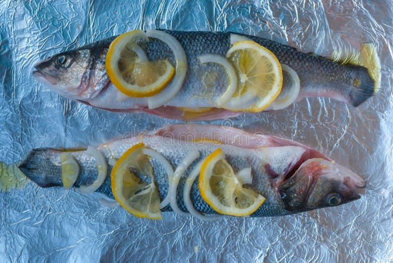 Dos pescados precortados en la hoja Limón, rebanadas de la cebolla, aceite de oliva Ahora usted necesita cocer en un horno foto de archivo libre de regalías