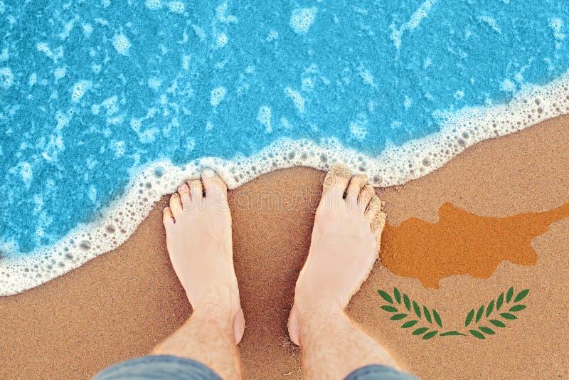 Dos pies en la playa arenosa soleada con la bandera Chipre Opinión superior sobre la resaca imagen de archivo