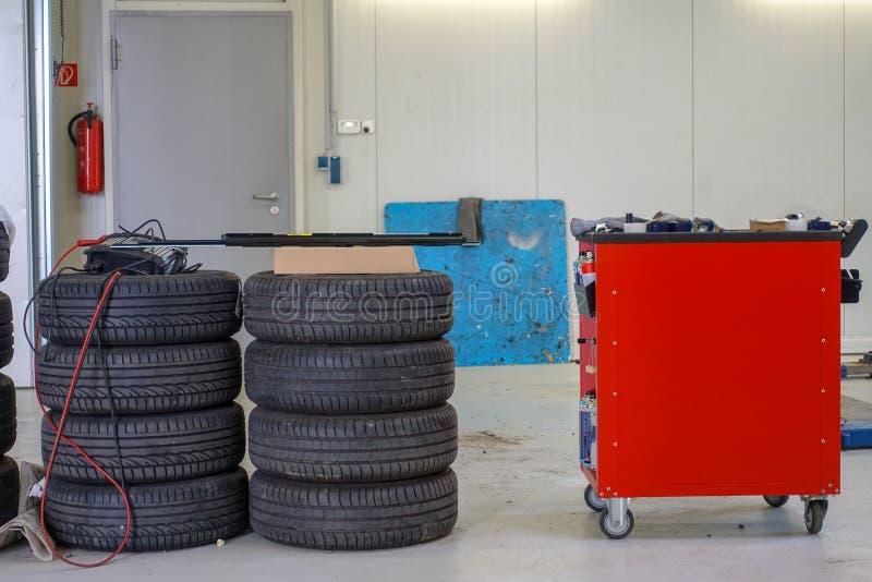 Dos pilas de neumáticos de coche y de una carretilla de la herramienta imagen de archivo libre de regalías