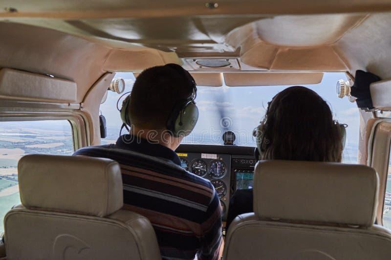 Dos pilotos que se sientan en una carlinga del aeroplano del skyhawk 172 de Cessna foto de archivo
