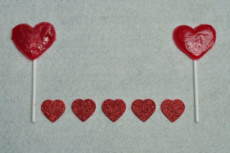 Dos piruletas de la forma del corazón con una fila de los corazones del brillo fotografía de archivo libre de regalías