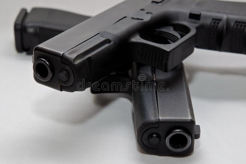 Dos pistolas semi automáticas negras, 9m m y un calibre 40 con uno encima del otro fotografía de archivo libre de regalías