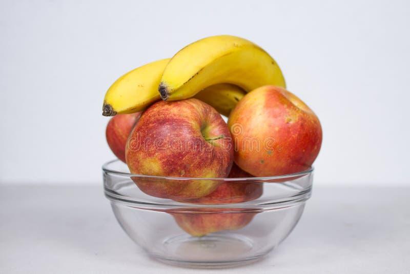 Dos plátanos y cuatro manzanas en la composición aislada bol de vidrio en el fondo blanco imagen de archivo