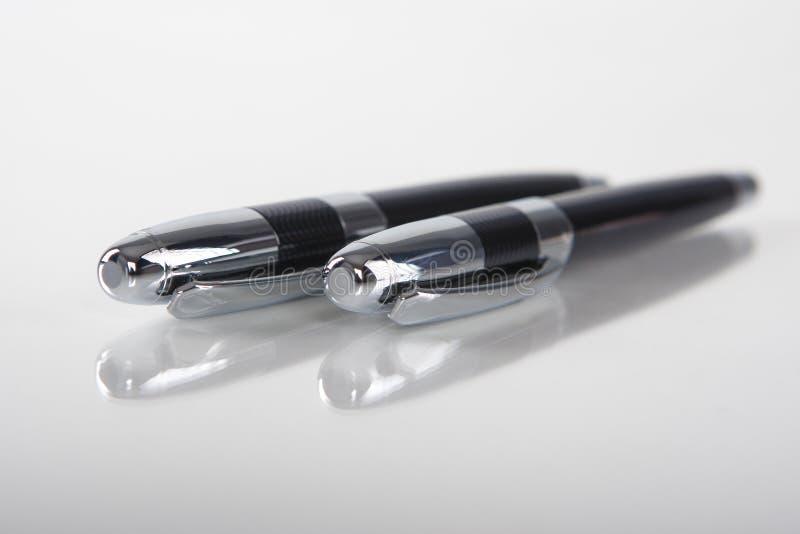Dos plumas negras del metal aisladas en el fondo reflexivo blanco fotos de archivo libres de regalías