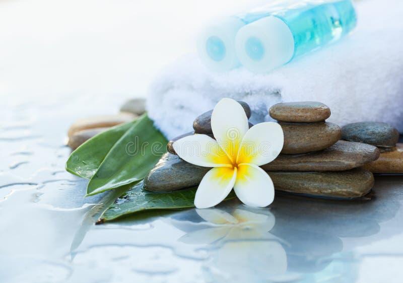 Dos poca botella con el aceite para el cuerpo con la flor imagen de archivo