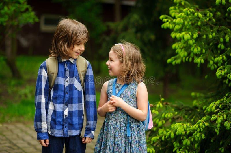 Dos pocos estudiantes de la escuela comunican alegre en el patio imagenes de archivo