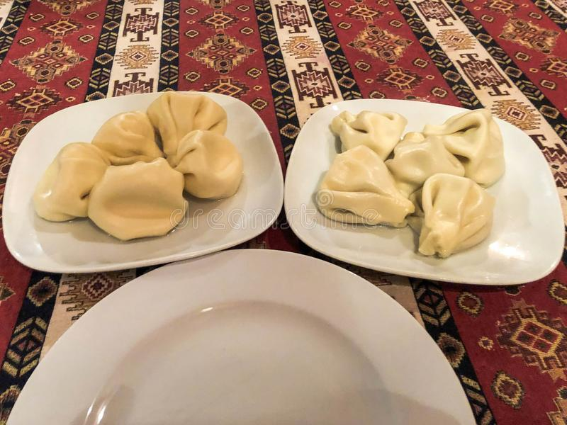 Dos porciones de alimentar el khinkali sabroso, manti en las placas blancas de cerámica en la tabla en el restaurante georgiano n imagenes de archivo