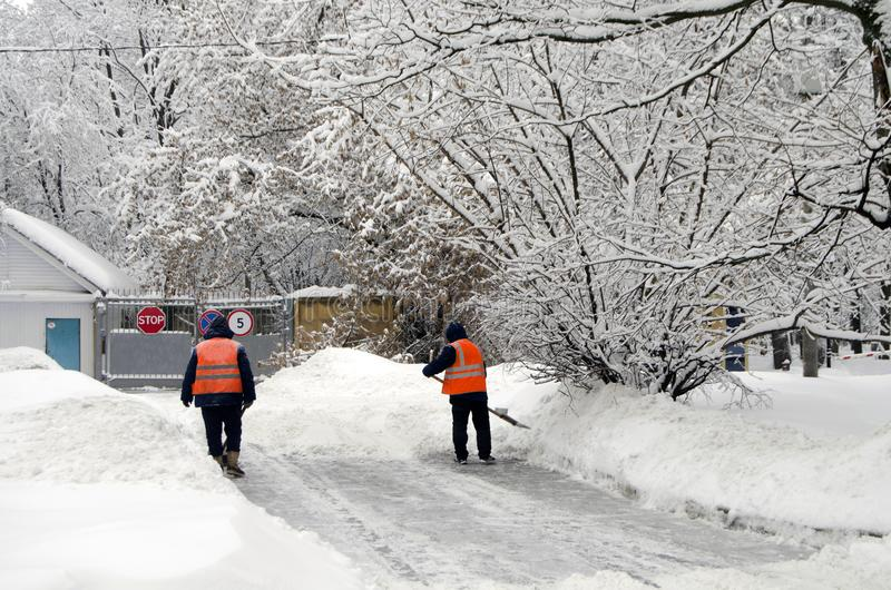 Dos porteros limpian nieve después de nevadas en Moscú Rusia el 4 de febrero de 2018 fotos de archivo