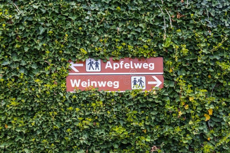 Dos postes indicadores que dirigen a caminantes a la trayectoria de Apple, y a la trayectoria del vino, en alemán, Apfelweg y Wei imagenes de archivo