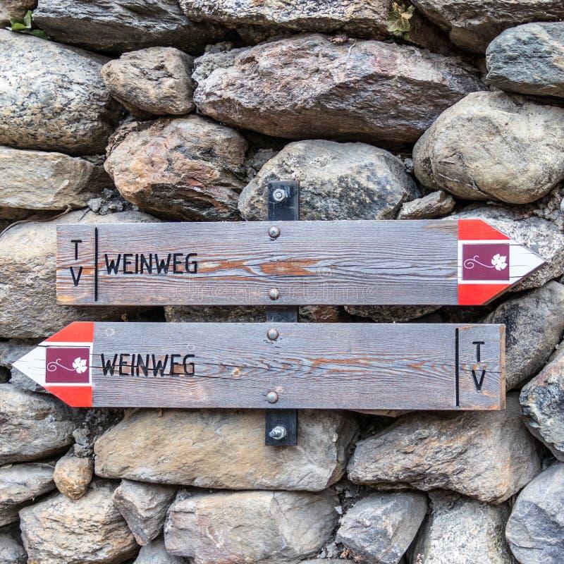 Dos postes indicadores que dirigen a turistas al camino del vino, en alemán, Weinweg, practican obstruccionismo en el fondo Opini imágenes de archivo libres de regalías