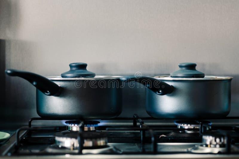 Dos potes de cocinar brillantes negros en un avellanador del gas que cuece al vapor como cocinan la comida dentro fotos de archivo libres de regalías
