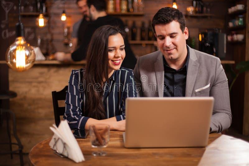 Dos programadores están trabajando juntos en un proyecto en una cafetería de su ordenador portátil imagen de archivo