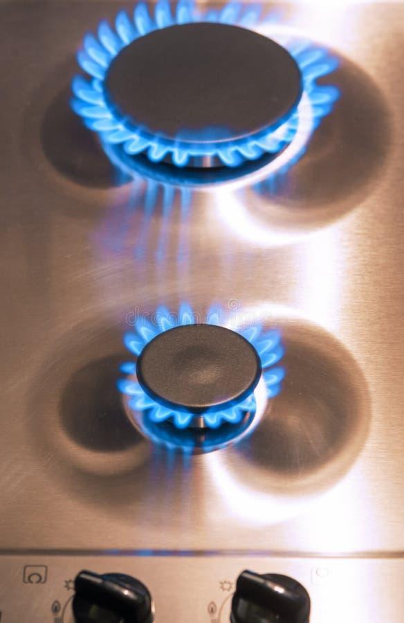 Dos quemadores de gas con las válvulas del regulador en superficie de la estufa fotografía de archivo