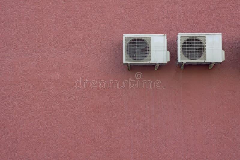Dos radiadores blancos del aire acondicionado en un muro de cemento granular rojo Textura de la superficie ?spera imagenes de archivo