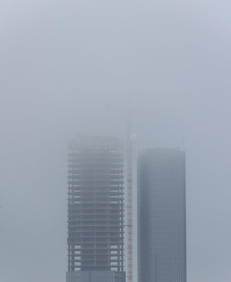 Dos rascacielos grandes bajo construcción rodeada por la niebla con humo fotografía de archivo libre de regalías