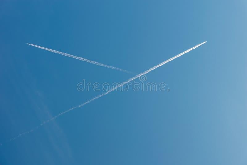 Dos rastros de los aeroplanos que cruzan contra el cielo azul fotos de archivo libres de regalías