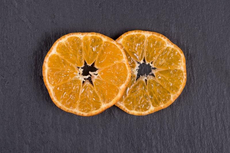Dos rebanadas de mandarín mienten en pizarra negra Concepto de sano, orgánico, comida del vegano, vitaminas Visión superior Naran foto de archivo libre de regalías