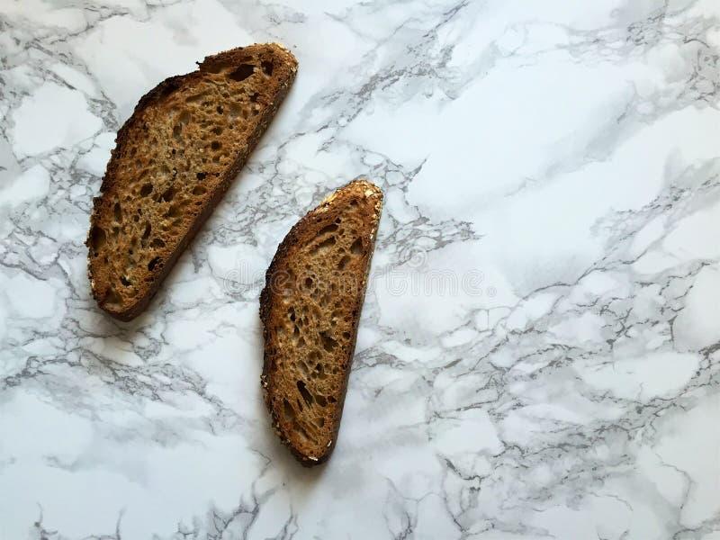 Dos rebanadas de pan artesanal del trigo integral del pan amargo en la encimera de mármol foto de archivo