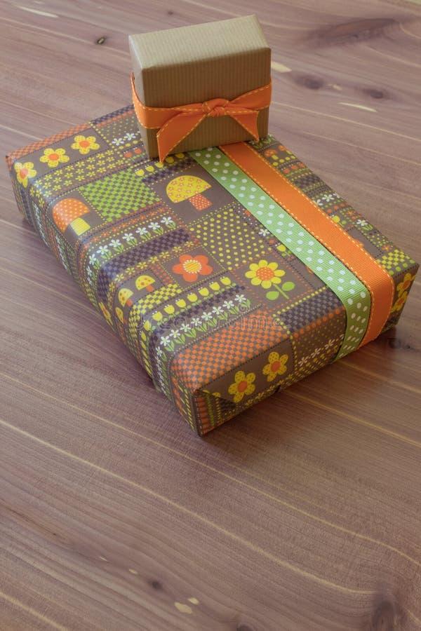 Dos regalos en papel de embalaje del vintage con las flores y setas, fondo de madera marrón y anaranjado, neutral verde foto de archivo