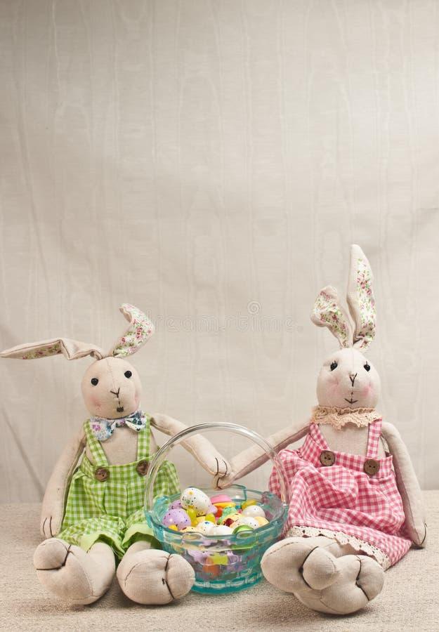 Dos rellenos, conejo de pascua del bebé y cesta de pascua de caramelo fotos de archivo