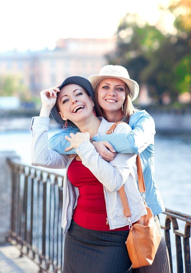 Dos risas y abrazos hermosos de las muchachas en la ciudad foto de archivo libre de regalías