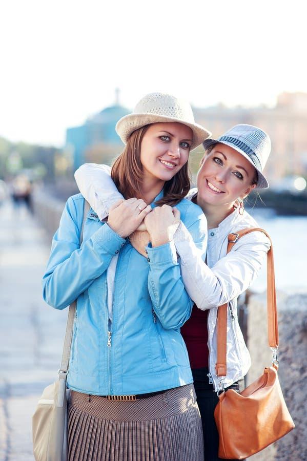 Dos risas y abrazos hermosos de las muchachas en la ciudad fotografía de archivo