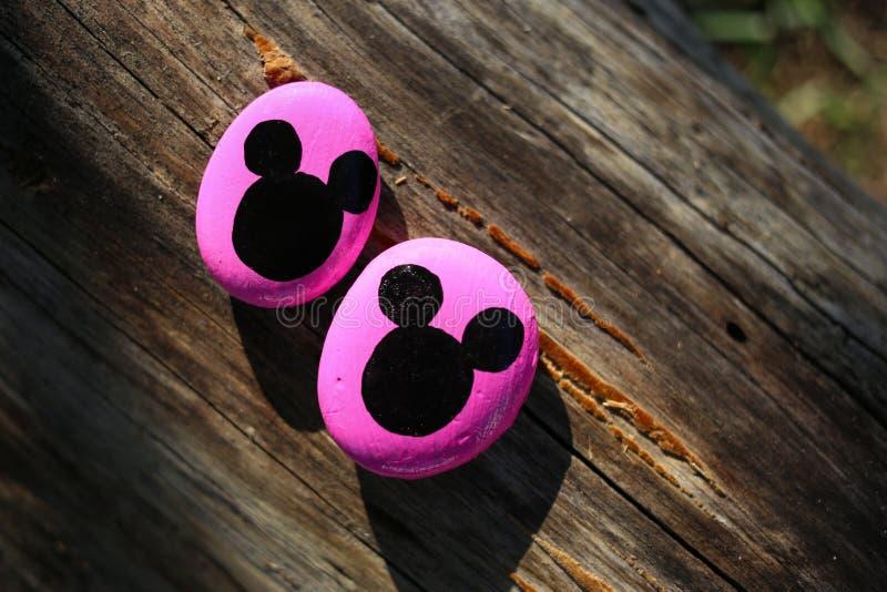 Dos rocas pintadas rosadas con las cabezas negras de Mickey Mouse fotos de archivo