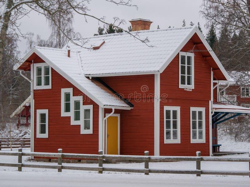 Dos rojos suecos storeywooden a la familia que emergieron las casas detrás de un árbol nevado junto a la nieve camino en el área  imagenes de archivo