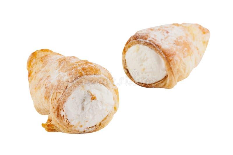 Dos rollos cocidos del soplo con la crema aislada en el fondo blanco imagenes de archivo
