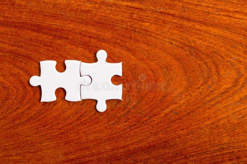 Dos rompecabezas blanco se coloca en los tableros de madera , Negocio común C fotos de archivo
