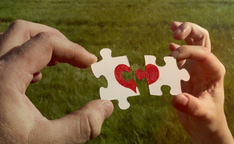 Dos rompecabezas de la cartulina con un corazón rojo pintado se llevan a cabo en las manos foto de archivo