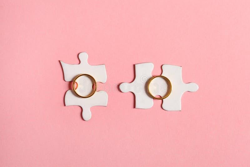 Dos rompecabezas de los trozos de papel con los anillos de bodas de oro aislados en el fondo rosado, visión superior fotografía de archivo