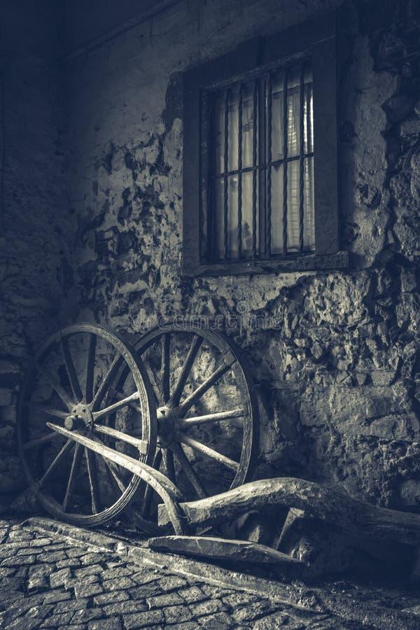 Dos ruedas de carro viejas cerca de una pared antigua fotos de archivo