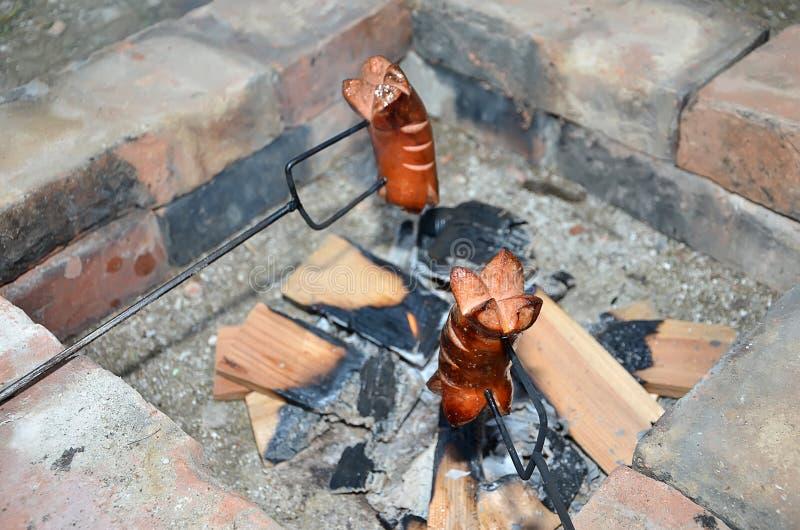 Dos salchichas de asado a la parilla sobre un fuego en verano imagenes de archivo