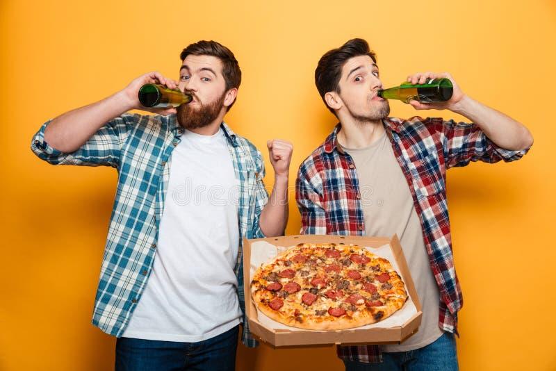Dos satisficieron a los hombres en camisas que bebían la cerveza mientras que sostenían la pizza imagen de archivo