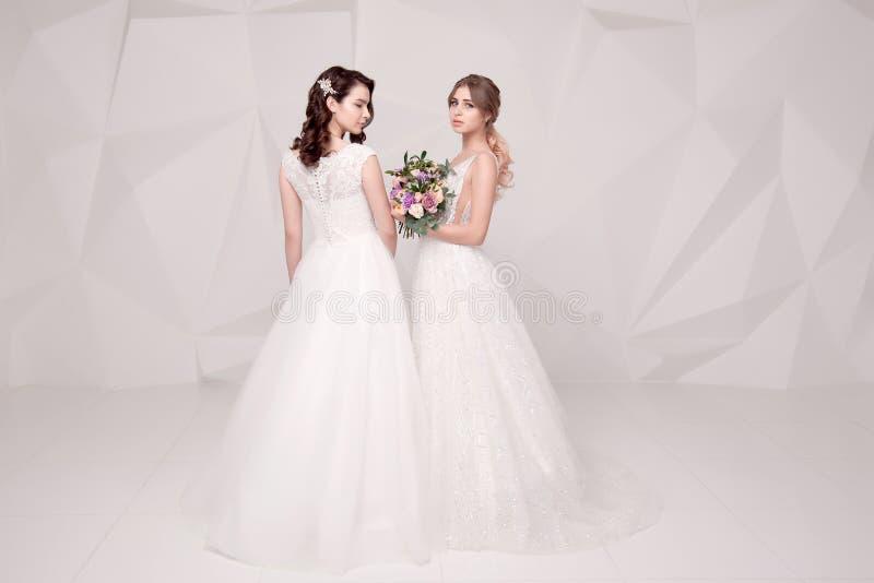 Dos señoras adorables que llevan en los vestidos de moda largos que sostienen las flores fotografía de archivo