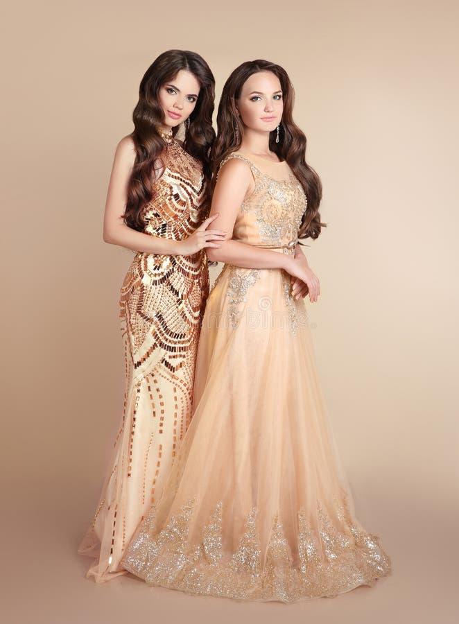 Dos señoras de la manera Las mujeres hermosas con el pelo ondulado llevan adentro de largo imágenes de archivo libres de regalías