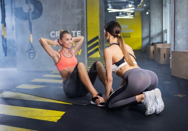 Dos señoras delgadas están entrenando juntas en club de deporte foto de archivo libre de regalías