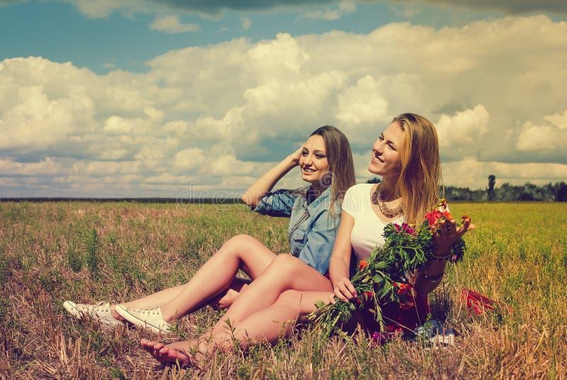 Dos señoras jovenes hermosas que se sientan con las flores encendido fotos de archivo libres de regalías