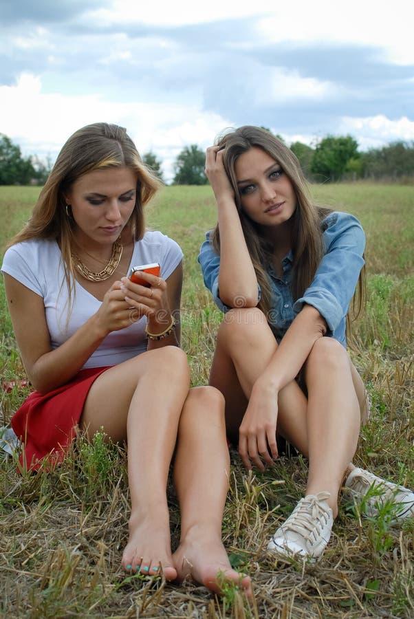 Dos señoras jovenes hermosas que se sientan junto encendido imagenes de archivo