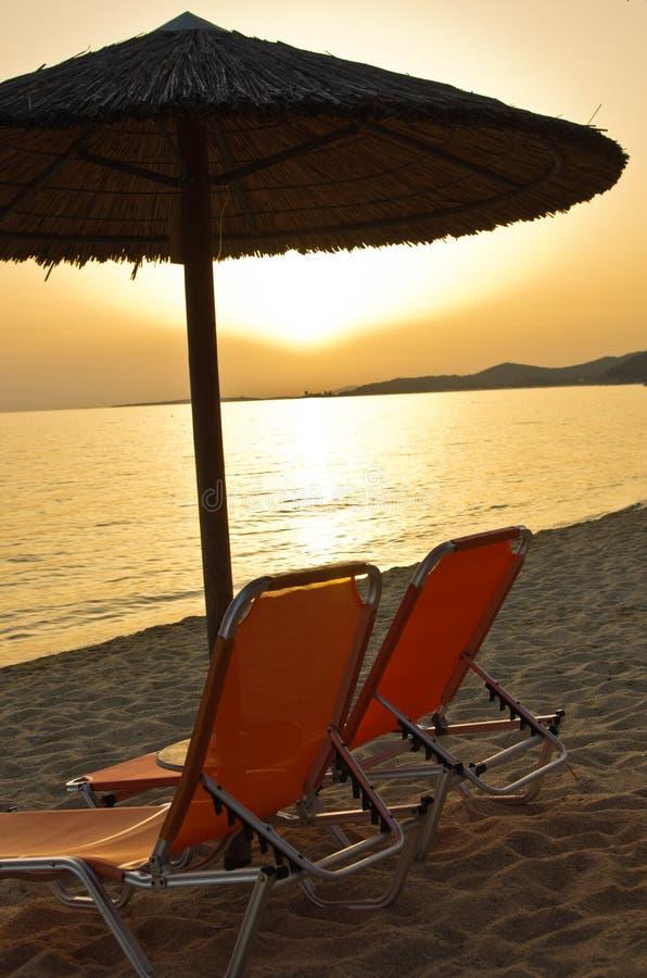 Dos sillas anaranjadas y parasoles perdidos en una playa en la puesta del sol, costa oeste de Sithonia imagen de archivo libre de regalías