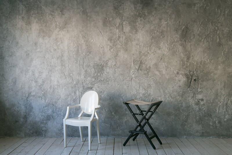 Dos sillas contra el muro de cemento gris Sitio en estilo del desván Suelo de madera Luz del día Espacio libre para el texto foto de archivo libre de regalías