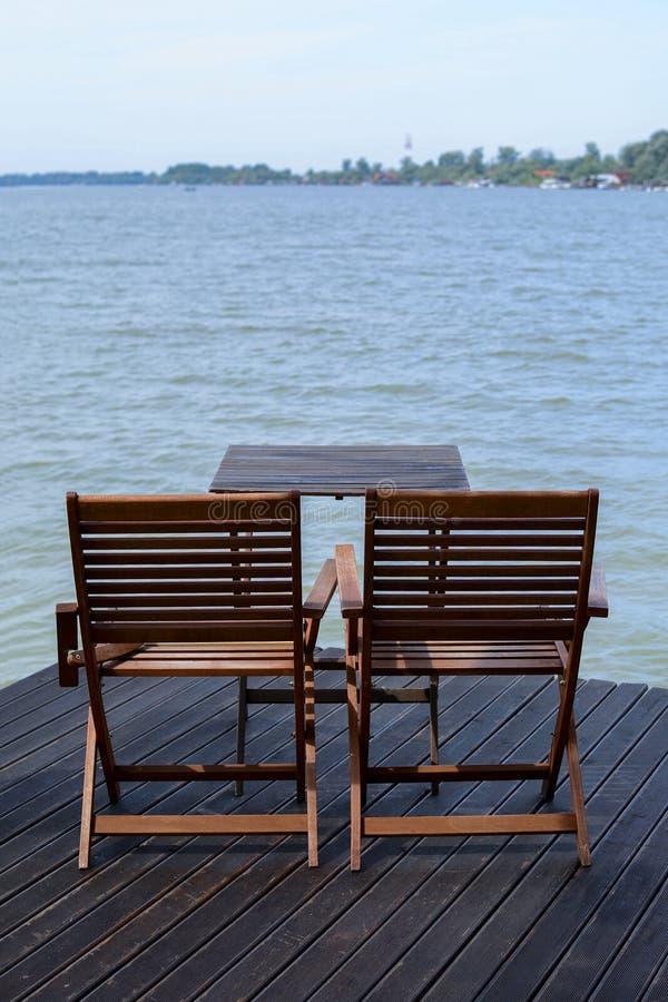 Dos sillas de madera en el muelle cerca del agua foto de archivo