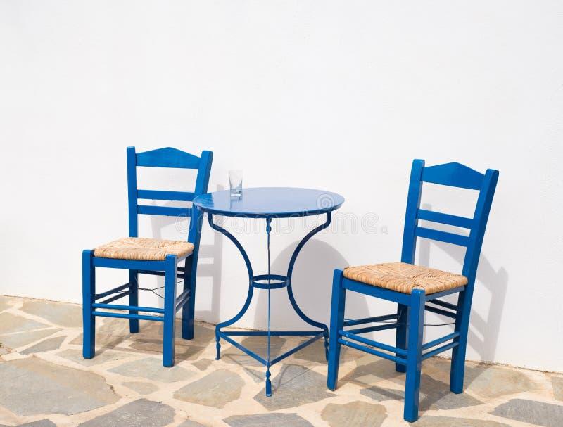 Dos sillas de madera tradicionales y una tabla del metal al aire libre fotos de archivo libres de regalías