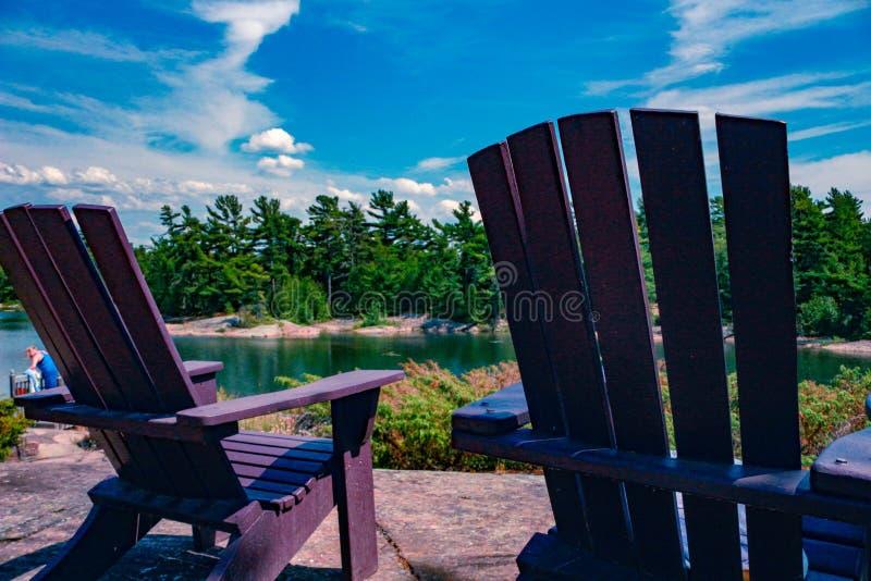 Dos sillas de Muskoka que se sientan en un muelle de madera que hace frente a un lago tranquilo A través del agua es una cabaña b fotografía de archivo libre de regalías