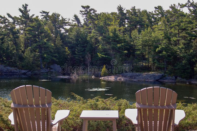 Dos sillas de Muskoka que se sientan en un muelle de madera que hace frente a un lago tranquilo A través del agua es una cabaña b imagenes de archivo