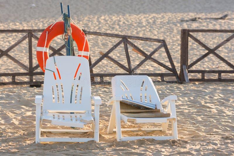 Dos sillas de playa viejas colocan la cuerda de salvamento cercana en la playa arenosa imagenes de archivo