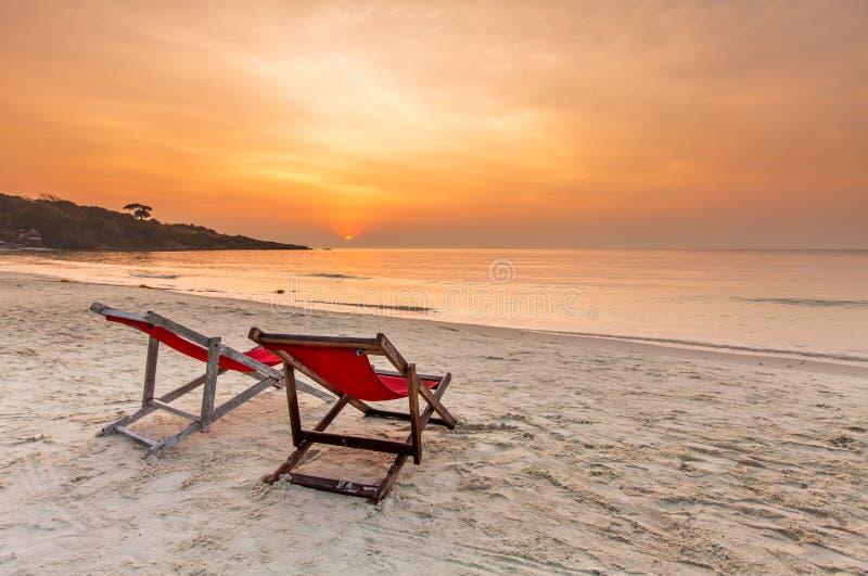Dos sillas en la playa y la puesta del sol foto de archivo