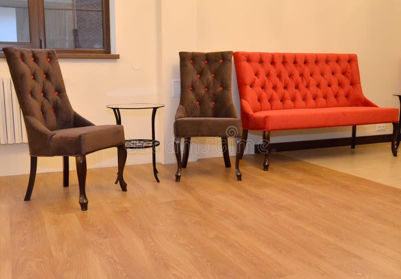 Dos sillas y sofás suaves se colocan en una pared en una sala de estar interno imagenes de archivo