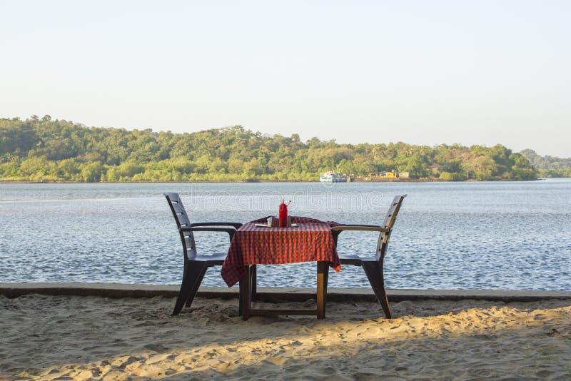 Dos sillas y una tabla con un mantel rojo contra la perspectiva de un río y de un restaurante verde del aire abierto del bosque imagen de archivo